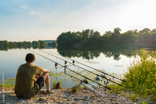 Fishing adventures, carp fishing. Angler is fishing with carpfishing technique in a beautiful summer day