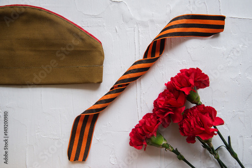 Poster  Carnation, George Ribbon, military binoculars and field cap
