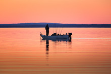 One Man Fishing From Small Boat At Sunset