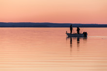 Two People Fishing From Small Boat At Sunset