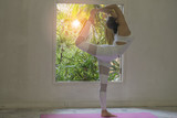 Young woman practicing yoga with indoor home interior background,