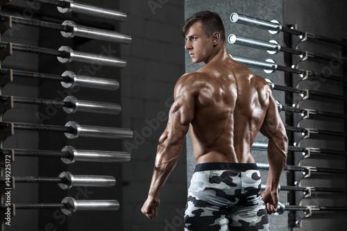 Zdjęcie XXL Tylni widoku mięśniowy mężczyzna pozuje w gym, pokazywać z powrotem i triceps. Silny męski nagi tors, wypracowany