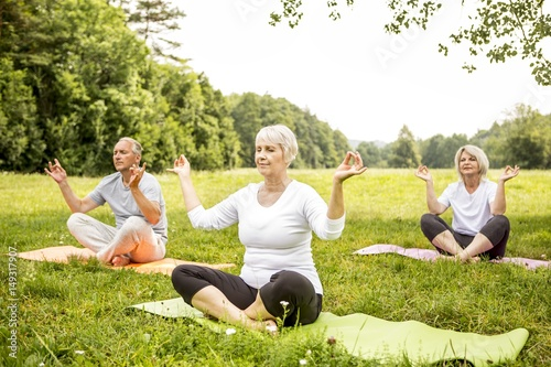 three people doing yoga in field buy this stock photo and explore