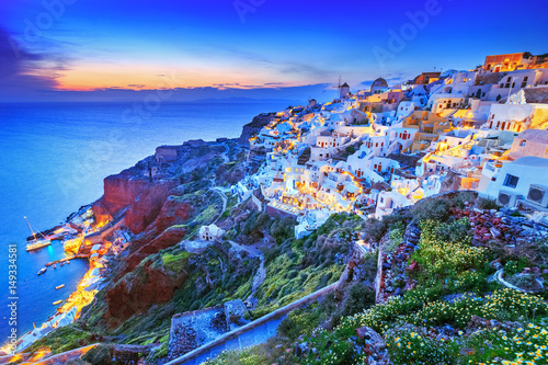 Fototapeta Classical view from sunset point over Oia village white and blue architecture, Santorini island, Greece. Incredible evening scenery. Santorini is popular European travel destination for honey moon. obraz
