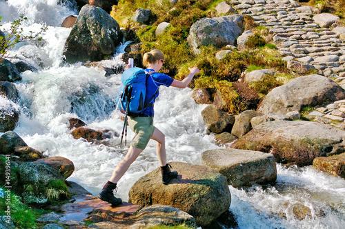 Fototapeta Female hiker crossing a mountain stream on stepping stones