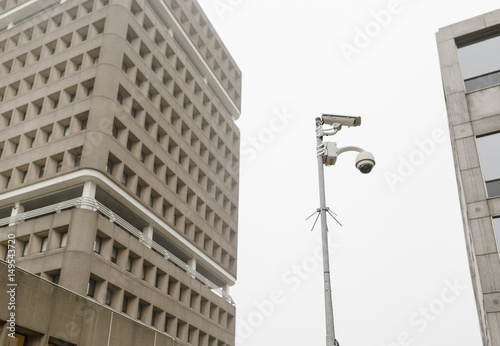 View of security camera on a pole between buildings