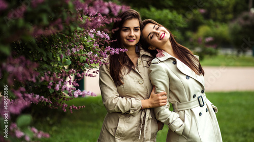 Photo  Two beautiful twins young women in trench coats near blooming lilac