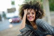 Leinwanddruck Bild - Young black woman with afro hairstyle smiling in urban background