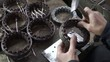 Mechanic repairing electric motor stator. Aligns with a hammer.