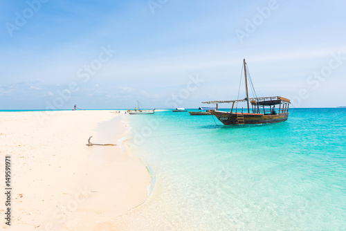 Foto op Aluminium Zanzibar anchored boat on african seashore with blue sky on the background