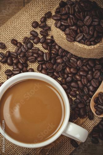 goraca-filizanka-z-kawowymi-fasolami-na-drewnianym-stole-i-czarnym-tle-rocznika-koloru-stylowy-sk