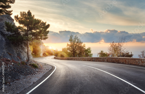 Asphalt road. Landscape with rocks, sunny sky with clouds and beautiful mountain road with a perfect asphalt at sunrise in summer. Vintage toning. Travel background. Highway in european mountains