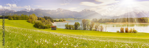 panorama scene in Bavaria, Germany at alps mountains with lake and sun beams