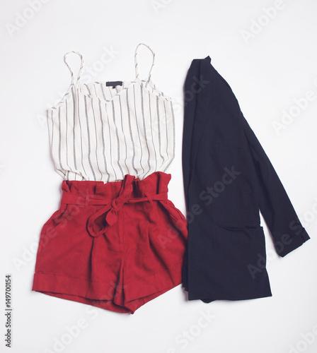 Obraz na płótnie Letni strój z białymi spodenkami w paski, czerwonymi spodniami i czarnym blezerem na białym tle. Płaskie leżało. Widok z góry.
