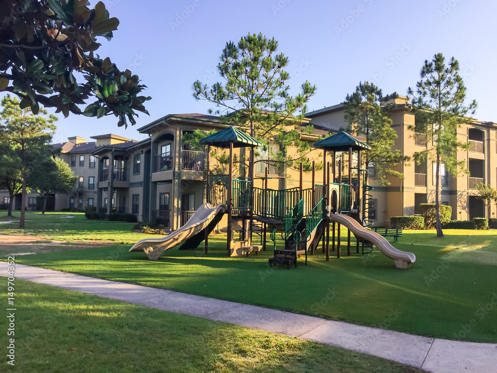 Fototapety, obrazy: A typical apartment complex building with a central playground swing, stairs in suburban area at Humble, Texas, US. View from grassy backyard, surrounded by green trees in early morning with blue sky.