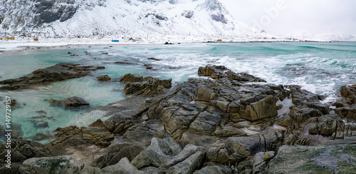 Fotografie, Obraz  Sunrise on the stone shore of the ocean and mountains with snow on the horizon
