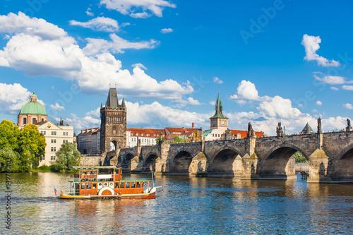 Staande foto Praag Prague, Czech Republic, Charles Bridge across Vltava river on which the ship sails