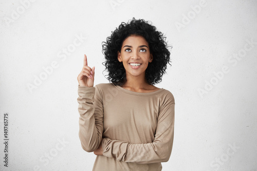 Fotografie, Obraz  Waist up shot of joyful girl wearing beige long sleeve t-shirt looking up, pointing finger at copy space above her head