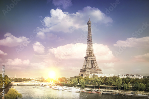 Poster de jardin Tour Eiffel Eiffel tower sunset with clouds. Romantic sunset background. Old Monument with boats on Seine river in Paris, France.