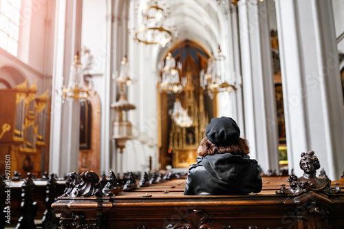 Obraz Alone woman sits on the bench in the church - fototapety do salonu