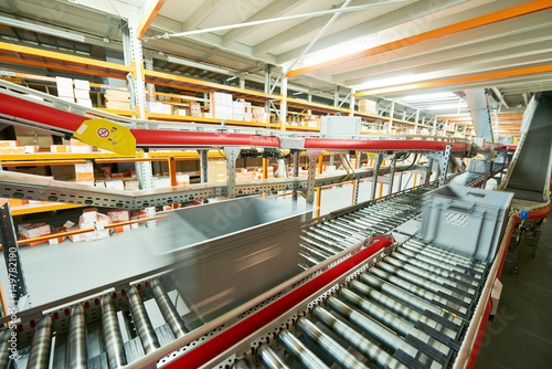 Fotografiet  Automated warehouse. Boxes with spare parts moving on conveyer