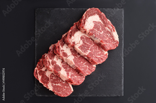 Photo  Fresh raw Prime Black Angus beef steaks on stone plate