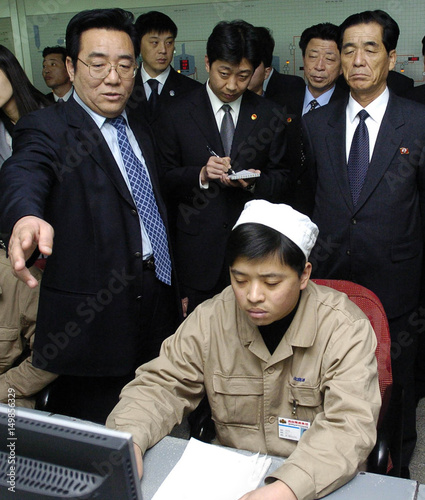 North Korea's Premier Pak listens to the general manager of