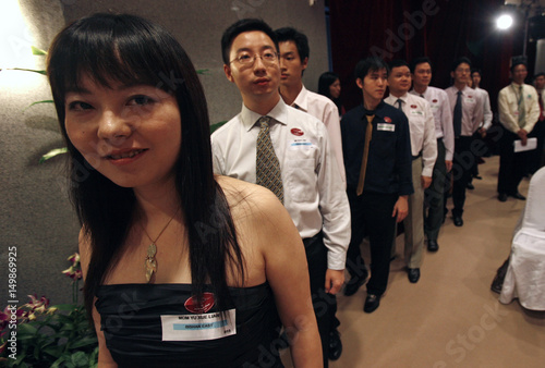 New Singapore citizen Yu Xue Lian waits in a line to receive her