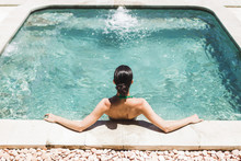 Woman In Green Swimsuit Relaxing In Outdoor Jacuzzi With Clean Transparent Turquoise Water. Organic Skin Care In Hot Bath In Luxury Spa Resort.