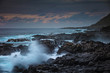 Rocky coastline with splashes of breaking waves at sunset time