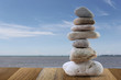 Balance Stones stacked to pyramid in sea and blue sky background.