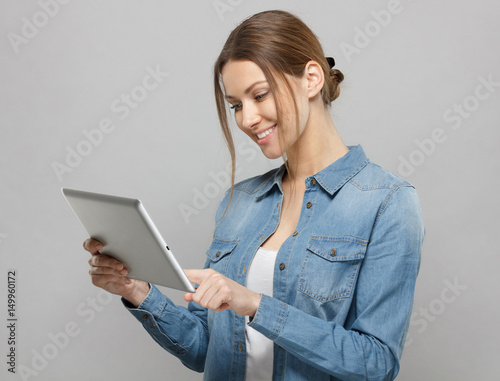 Valokuva  Side indoor portrait of good-looking young woman isolated on gray background turned left with tablet device in hand scrolling webpages on touchscreen with enthusiasm and lively optimistic smile