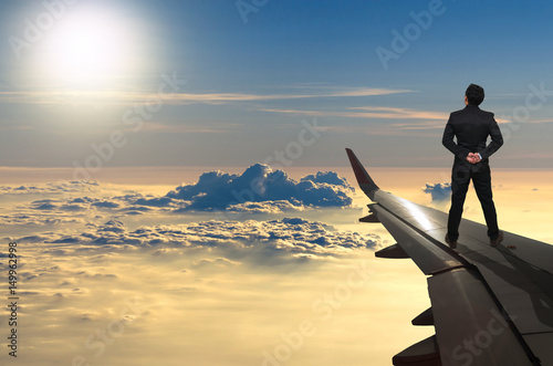 Fotografía  businessman standing looking the sunset on airplane wing, Challenge business con