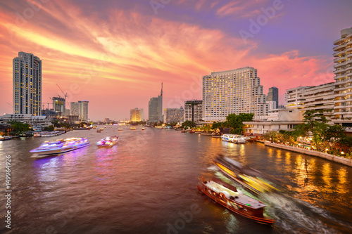 Bangkok city with business building and chao praya river with boat at twilight sunset, street view on Taksin Bridge, thailand Canvas Print