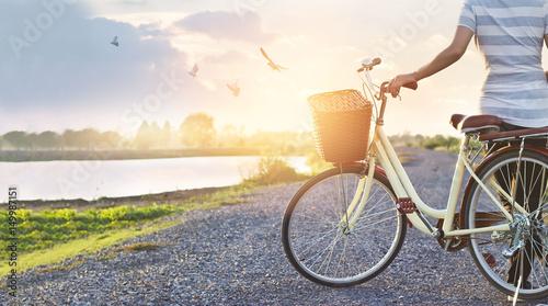 Zdjęcie XXL kobieta stojąca z rocznika rowerów, relaks w lecie zachód natura wiejski z latające ptaki