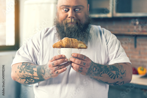Man looking at a croissant Fototapet