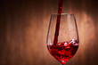 Close-up of tasty red wine pouring in the pure fragile wineglass standing against wooden background.