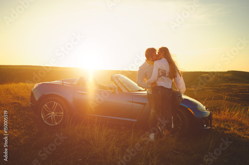 Happiness couple stay near the new sport car hugging and kissing at sunset