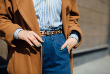 Closeup Of Hand Of Stylish Woman In Brown Coat Blue Striped Shirt, Blue Jeans With Tiger Pattern Belt. Fashionable Girl On The Street. Female Fashion
