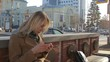 Woman sitting on bench using smart mobile phone reading at sunny city street