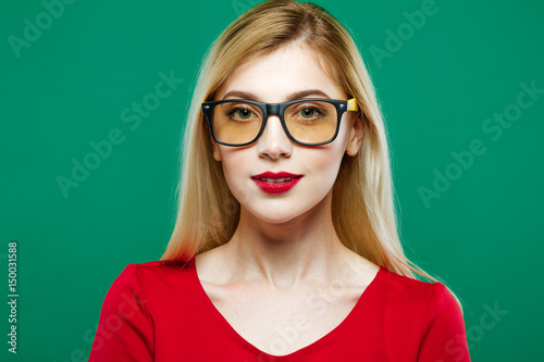 0d1705d32c Portrait of Cute Girl Wearing Eyeglasses on Green Background. Young Woman  with Red Sensual Lips and Long Hair in Studio.