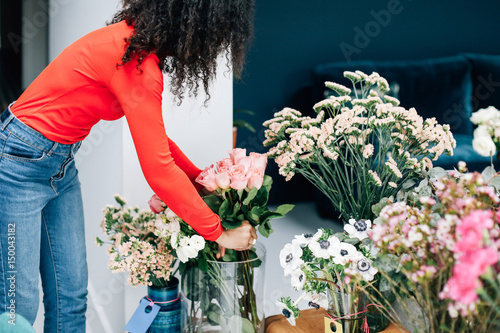 Female Florist Arranging Roses In Vase For Shop Display Buy This