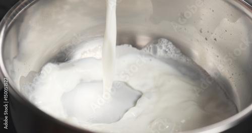 Fotomural shot of pouring milk into saucepan, 4k photo
