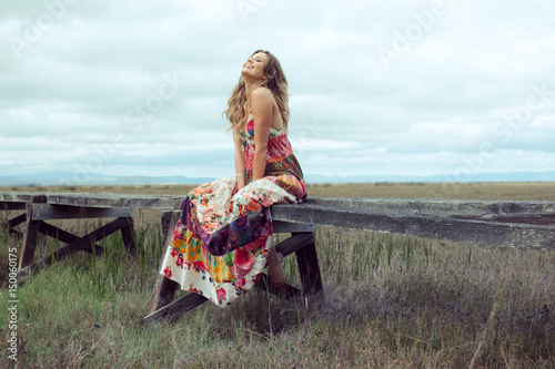 Young woman in boho maxi dress sitting on elevated wooden walkway in landscape Poster