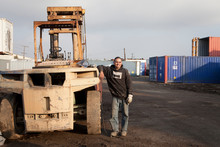Man On Construction Site Standing By Heavy Machinery