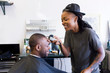 Female barber using hair clippers on male customer in barber shop