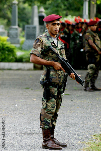 Sri Lankan army commando stands guard during funeral