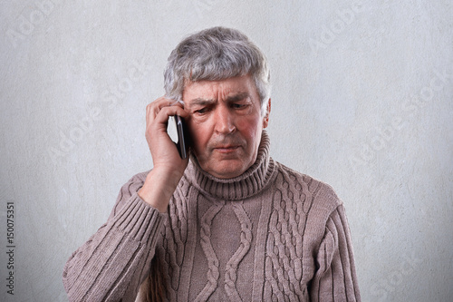 An Angry Mature Man With Gray Hair And Wrinkles Holding Smartphone