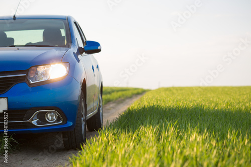 gomel-belarus-6-may-2017-blue-car-renault-logan-parked-in-a-field-on-a-country-road