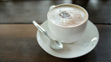 Hot mocca cofee in a cup with spoon and white dish, placed on wooden table